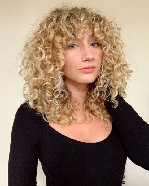 Medium Curly & Frizzy Hairstyle with Bouncy Bangs
