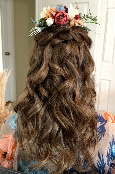 Wavy Half Up Half Down Hairstyle with Braided Crown and Floral Accessory