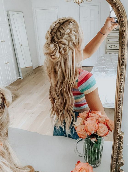 Wavy Half Up Half Down Hairstyle with Intricate Loose Side Braids and Messy Bun